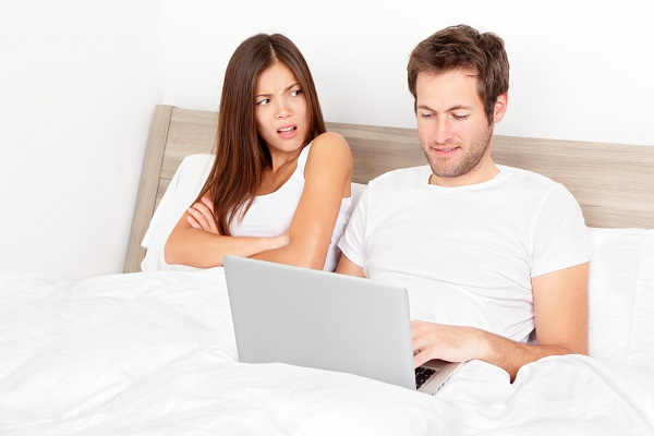 man on computer in bed