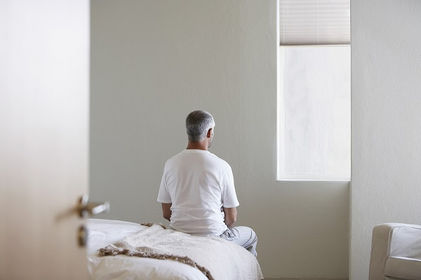 middle aged man sitting on bed