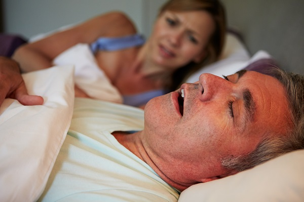 man asleep in bed next to woman